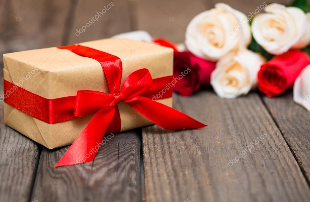 Gift box with blured red and white roses on a dark wooden backgr