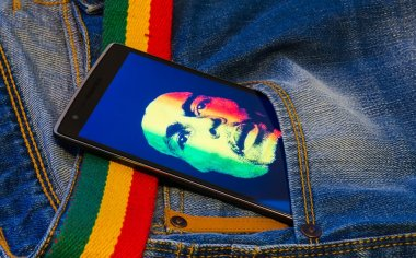 Blue jeans with smartphone with bob marley