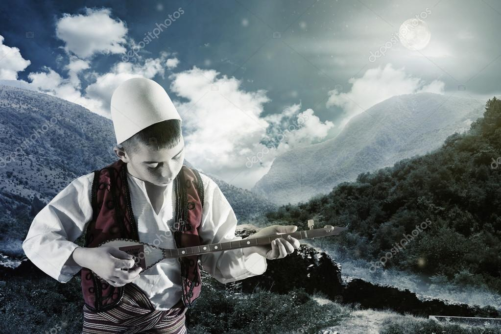 albanian musician kid playing string instrument outside in camp fire mood