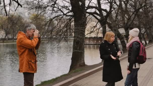 Adult man photographer take pictures of a woman and girl with old vintage film camera