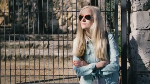 Osamělá dívka čeká pobyt na autobusové zastávce v bundě a sluneční brýle, doprava
