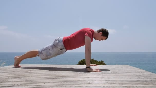 Athletic Caucasian man performs pushups on rocky coast beach on sunny day