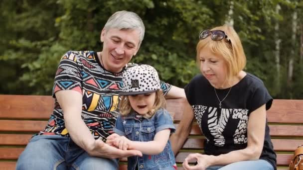 Grandfather and grandmother spending time with their granddaughter on a park bench