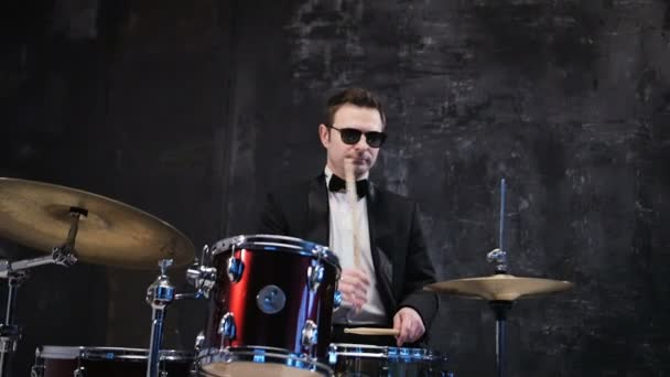 Man in black suit and sunglasses plays on drum. Rock cover band performing on stage with drummer