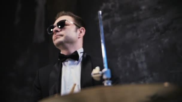 Férfi fekete öltöny és a napszemüveg játszik a dob. Teljesít a színpadon, a dobos rock zenekar
