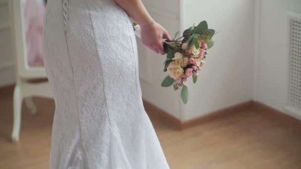 Krásná nevěsta s kyticí u zrcadla