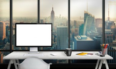 Isolated computer display for mockup in office interior overlooking the city and skyscrapers. Work desk with keyboard, mouse, cup of coffee, paper, pencils.