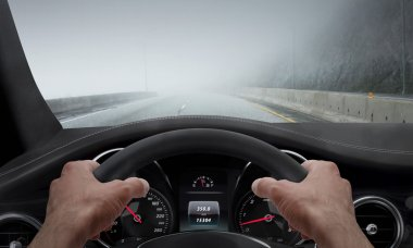 Driving in fog weather. View from the driver angle while hands on the wheel