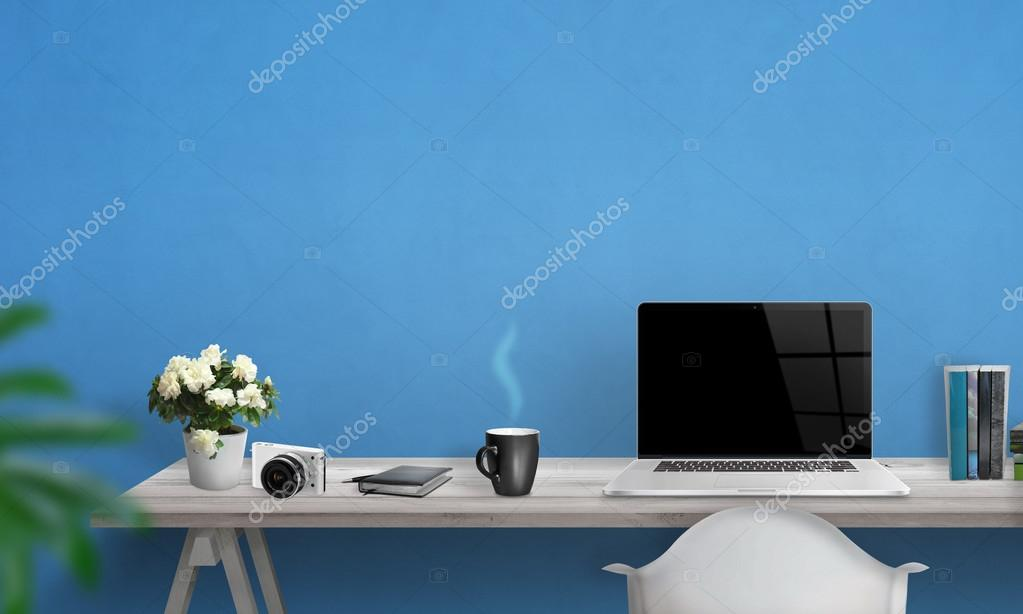 Laptop with blank screen on office desk. Free space on wall for text. Blue wall in background.