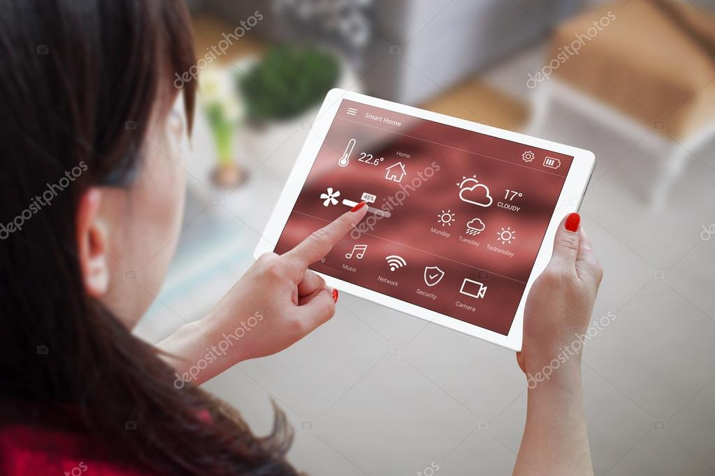 Woman use application for smart home control on tablet. Interior of living room in the background.