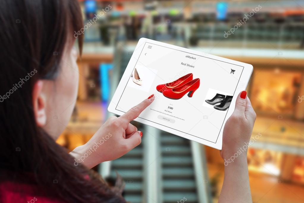 c5f27d0cb Mulher compras on-line com o tablet. Mantendo o dispositivo e escolher sapatos  vermelhos