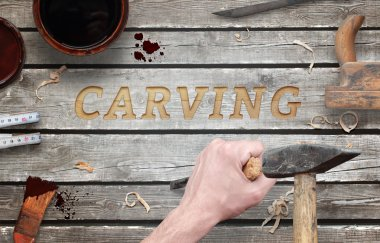 Carving word carved in wood with hammer and chisel. Beside is brush, paint, wood plane, ruler, shavings.