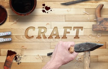 Craft word carved in wood with hammer and chisel. Beside is brush, paint, wood plane, ruler, shavings.