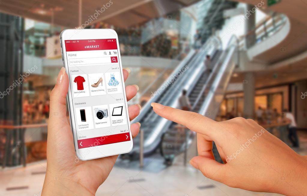e6b8364323df20 Slimme telefoon online winkelen in vrouw hand. Shopping center op  achtergrond. Kopen kleding schoenen accessoires met e-commerce website —  Foto van vlado85
