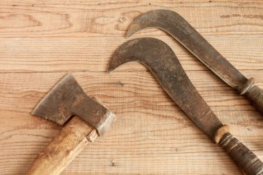 dated and used cleaver and two billhooks on wooden background