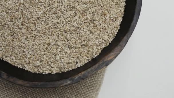 Sezamová semínka v rustikální dřevěné misky na pytloviny pozadí