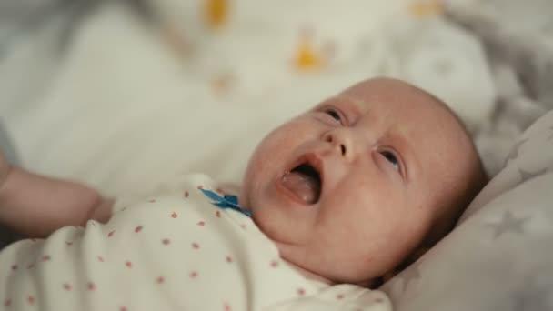 Novorozená holčička brečí ve své posteli