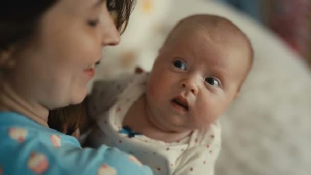Matka drží své novorozené dítě v náručí a jemně líbat jeho tváře