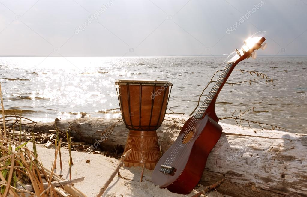 Ukulele & ethnic drum on a beach.