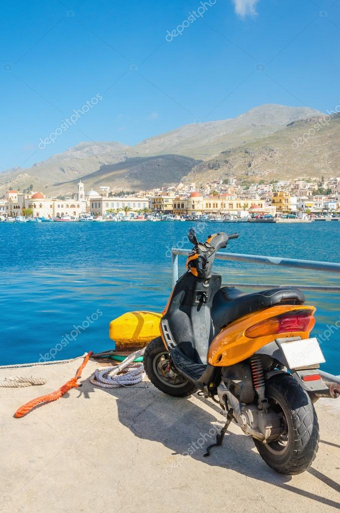 Orange scooter standing on wharf of Greek harbour