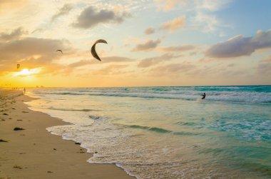 Professional kiter makes trick, sunset