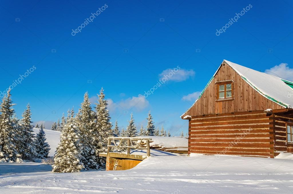 Wooden house in winter landscape, sunny day
