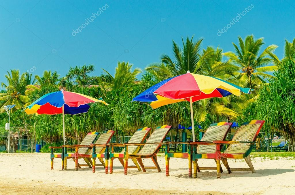 Exotic sandy beach with sun umbrellas and chairs
