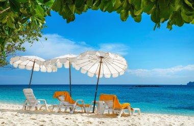 Sunbeds and orange towels under umbrellas Thailand