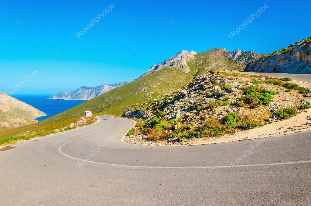 Road turn with sea coast on Greek island