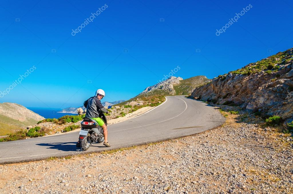 Man driving scooter on road turn in mountains