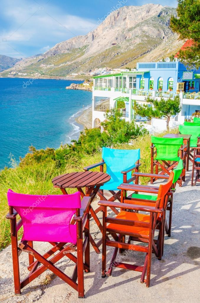 Colorful wooden chairs with view on sea, Greece