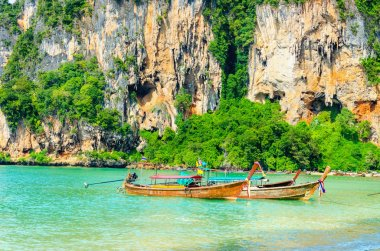 Beach with mogotes, long tail boat Krabi, Thailand