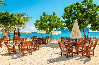 Wooden tables with sun umbrellas at luxury resort