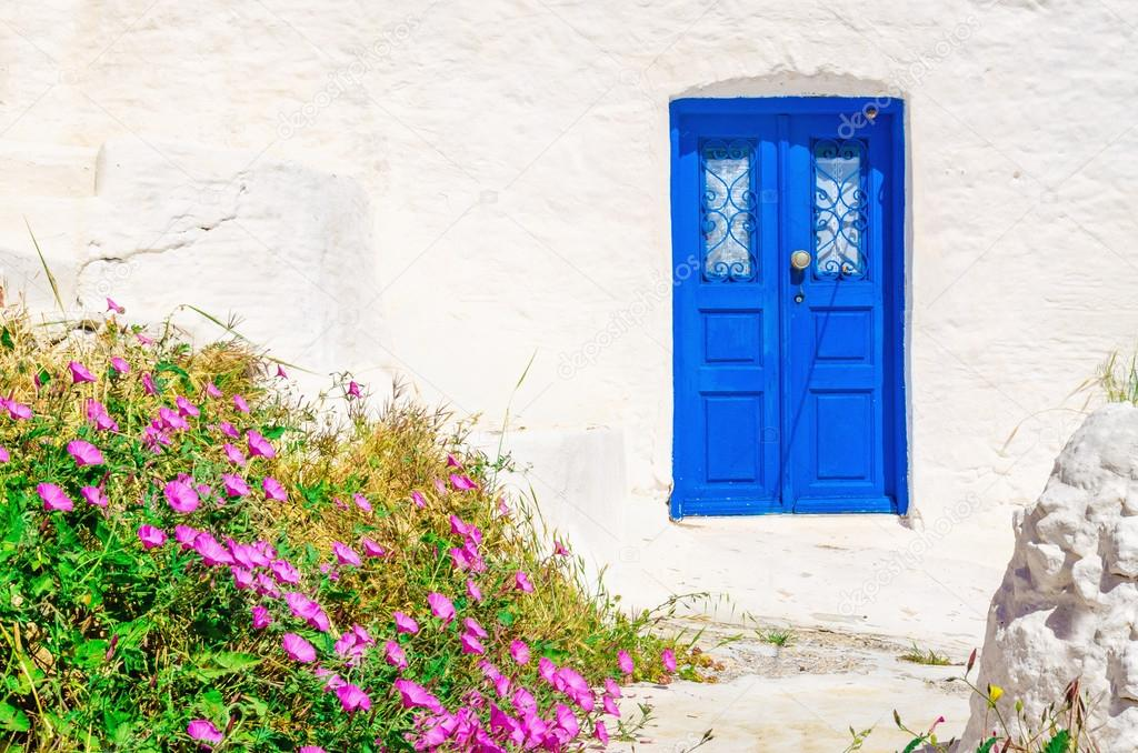 Blue wooden door, white wall and flowers, Greece