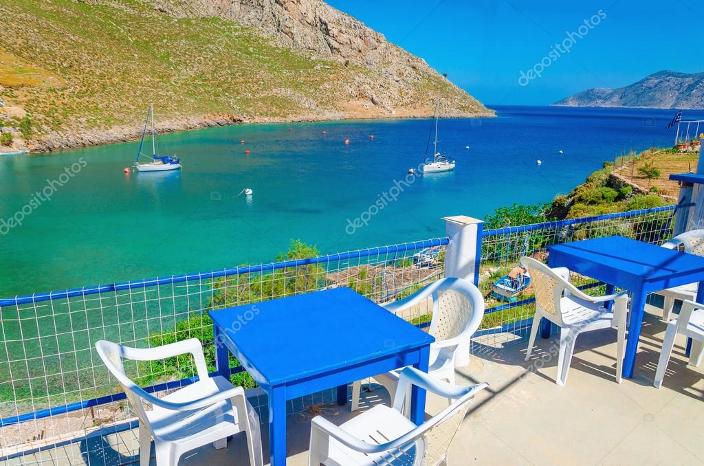Blue wooden tables and chairs in bay, Greek Island