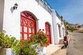 Fotografie rot Motorrad vor typischen griechischen Haus