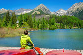 Photo Young man at pier mountain lake with high peaks