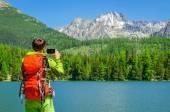 Fotografie man takes a photo of mountain lake