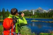 Fotografie man takes picture of mountains and lake