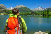 Fotografie man admires high mountains and lake