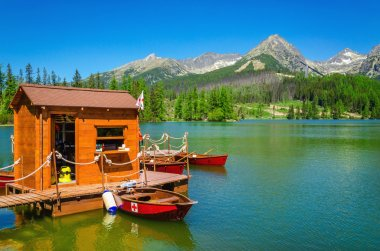 Wooden hut and red boats on mountain lake