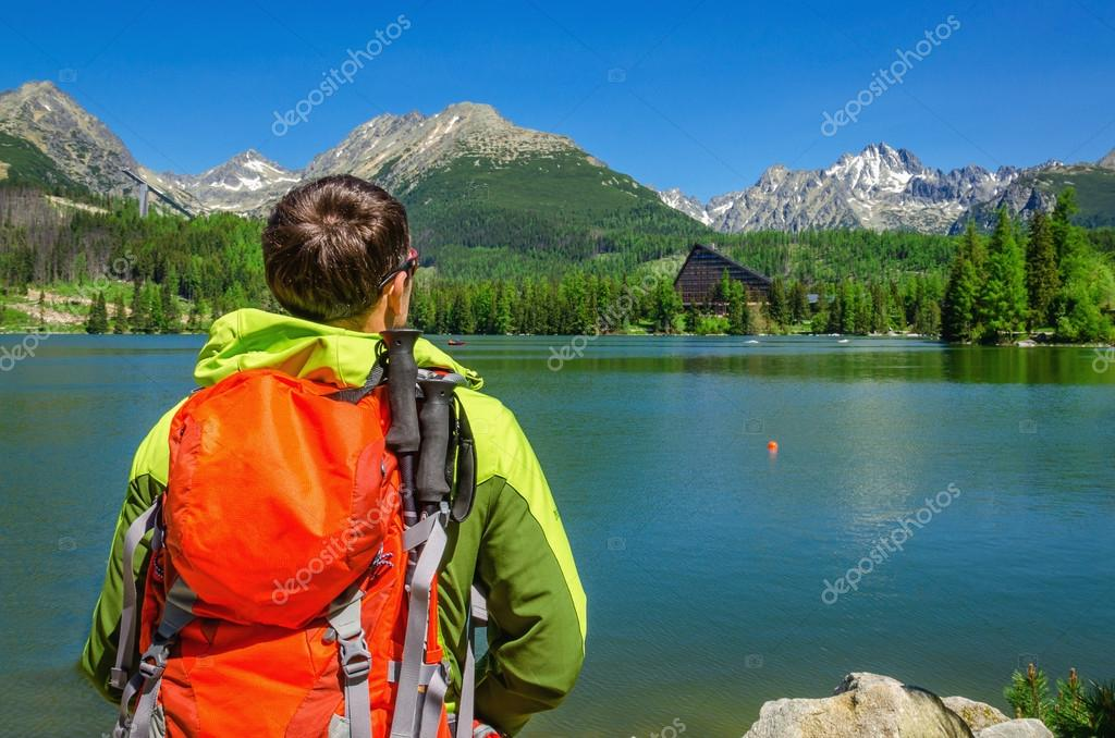 man admires high mountains and lake