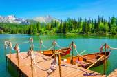 Photo Red wooden boats moored to pier of mountain
