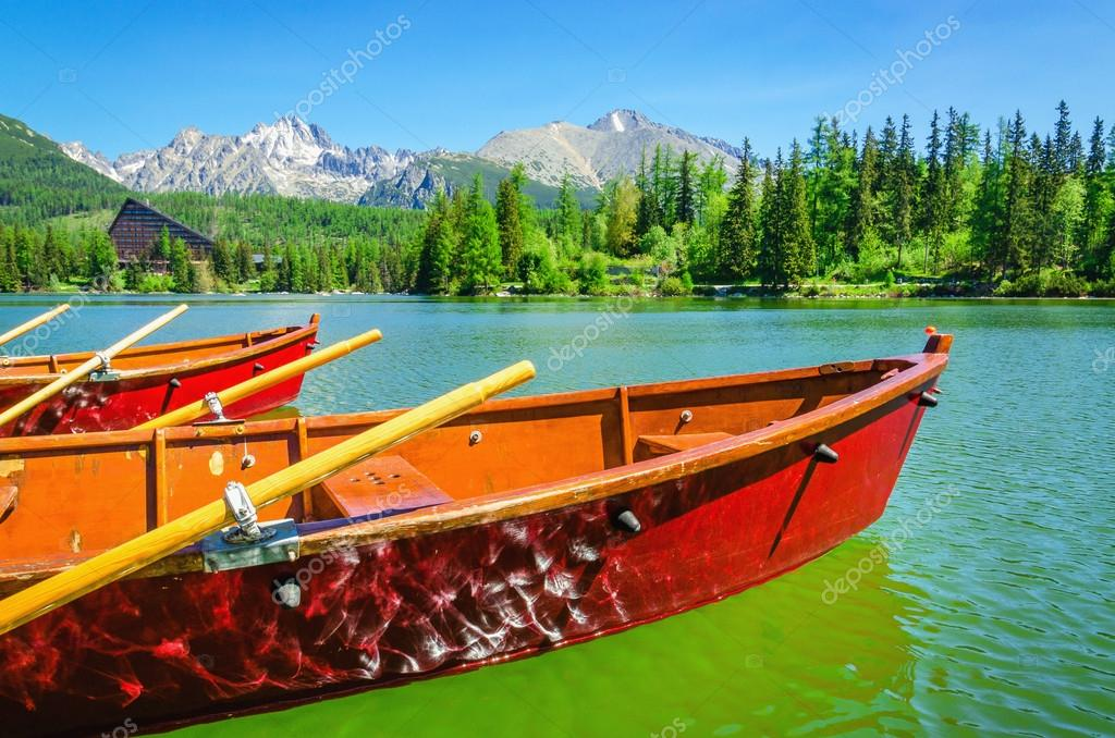Red wooden boats on mountain lake Strbske Pleso