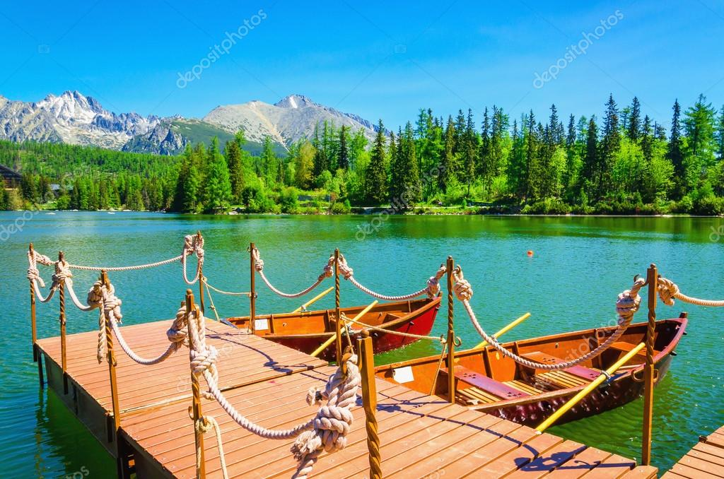 Red wooden boats moored to pier of mountain