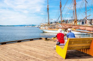 Pair of older people sitting on bench, Oslo Norway