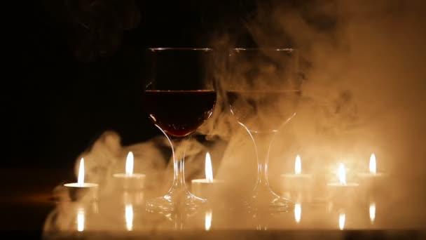 Sklenice na víno a hořící svíčky v kouři