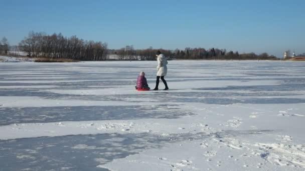 Mutter und Tochter rodeln auf zugefrorenem See