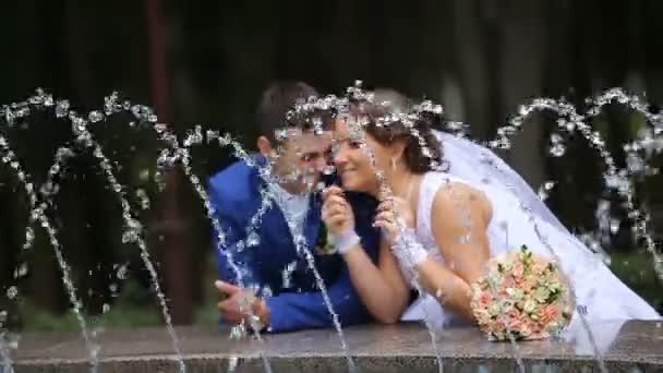 šťastné nevěsty a ženicha, stojící u fontány v parku