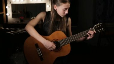 cute girl plays on the acoustic guitar with bright emotions